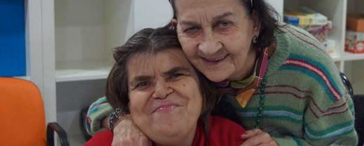 dos personas mayores se abrazan