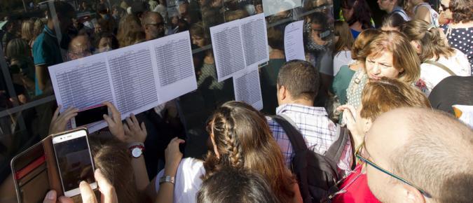 Personas mirando listas en el examen de oposiciones