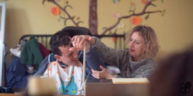 una mujer apoya a una persona a usar una máquina, le coge la mano