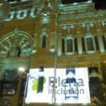 ayuntamiento de Madrid iluminado de verde y con el logo de Plena inclusión